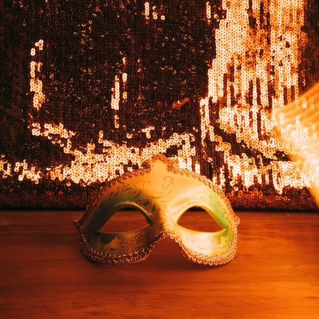Green carnival mask on wooden desk with golden glitter sequins Free Photo
