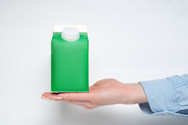 Green carton box or packaging of tetra pack with a cap in a female hand. Premium Photo