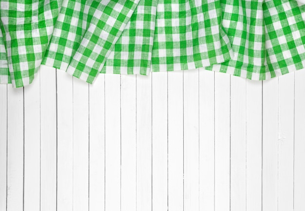 Green checkered tablecloth on wooden table, top view Premium Photo