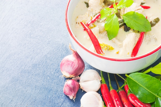 Green chicken curry with raw spicy ingredient thai traditional food on light blue background Free Photo