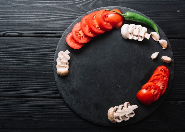 Green chili pepper; garlic cloves with slices mushrooms and tomatoes on black wooden surface Free Photo