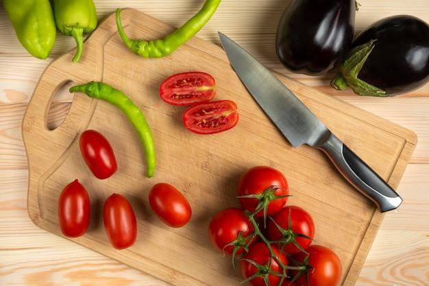 緑の唐辛子と木製のテーブルでスライスされたトマト 無料写真