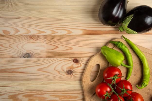 緑の唐辛子とトマトの木製のテーブル 無料写真
