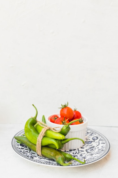 Green chilies and bowl of red tomatoes on ceramic plate against white background Free Photo