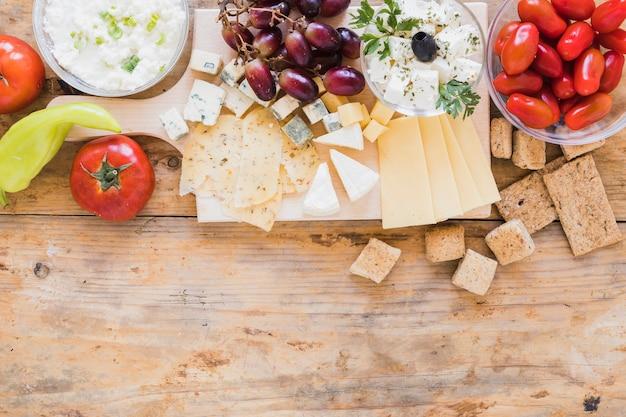 Green chilies pepper, tomatoes, grapes, crisp bread and cheese cubes on desk Free Photo