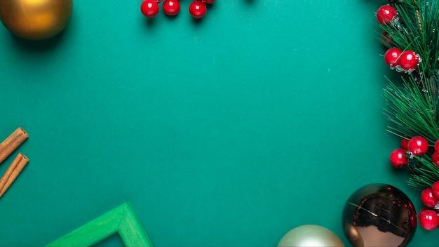 전나무 지점, 붉은 열매, 계 피, 크리스마스 장식품 또는 공 및 텍스트 또는 복사 공간에 대 한 장소의 프레임 그린 크리스마스 배경. 프리미엄 사진