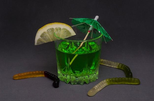Зеленый коктейль на хэллоуин, украшенный долькой лимона и декоративным зонтиком Premium Фотографии