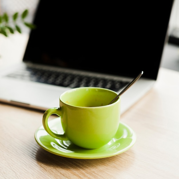 Green coffee cup and open laptop on wooden desk Free Photo
