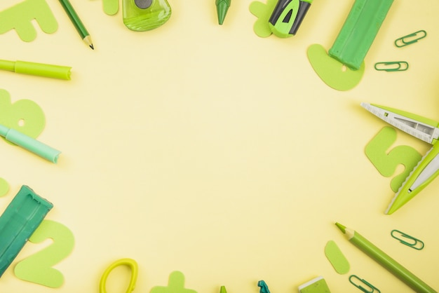 Green color school supplies arranged in circular shape over yellow background Free Photo