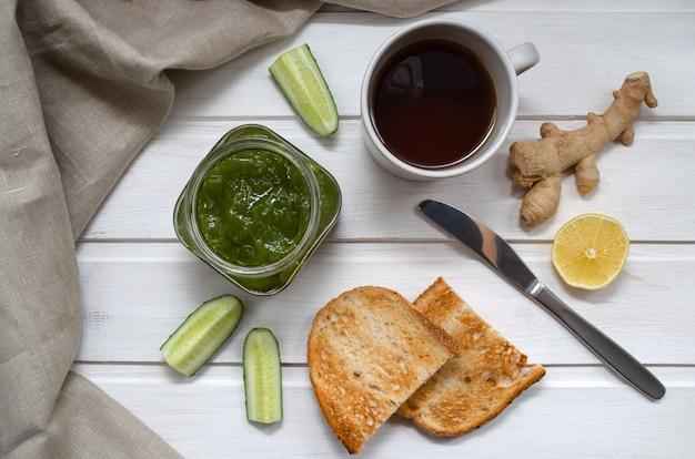 Варенье из зеленых огурцов в прозрачной банке с ломтиками огурца и имбиря с тостами, ножом и текстильной салфеткой на светлом деревянном столе. концепция здорового питания. Premium Фотографии