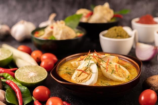 レモン、レモングラス、チリ、トマトのブラックカップに卵とグリーンカレー。 無料写真