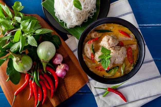 Green curry with fish ball on wooden background ,thai cuisine Premium Photo