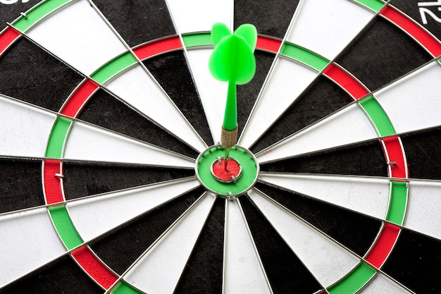 Green dart punctured in the center of the target Premium Photo