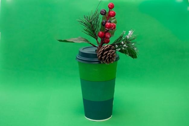 녹색 일회용 종이 컵과 녹색 배경에 붉은 열매와 소나무 콘 소나무 지점 프리미엄 사진