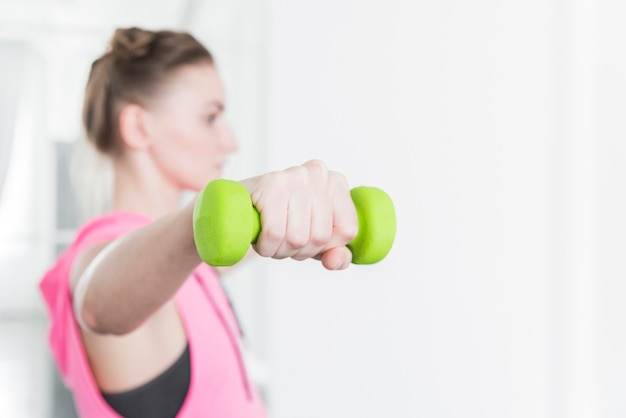 Green dumbbell lifted by woman in sportswear Free Photo