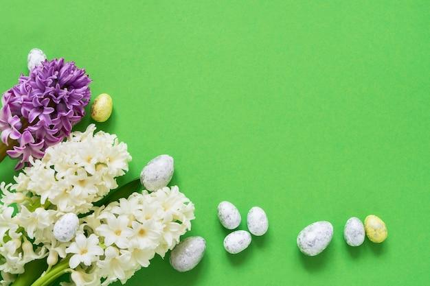 녹색 부활절 배경입니다. 봄 꽃과 녹색 배경에 장식 부활절 달걀. 공간 복사 프리미엄 사진