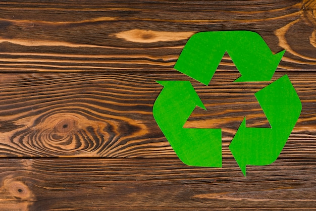 Green eco recycle logo on wooden background Free Photo