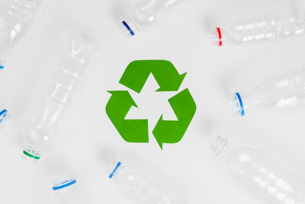Green eco recycle symbol and plastic bottles Free Photo