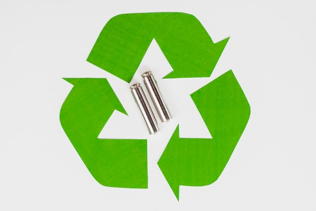 Green eco recycle symbol and used batteries Free Photo