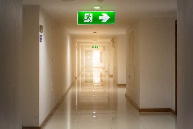 Green emergency exit sign in hotel showing the way to escape Premium Photo