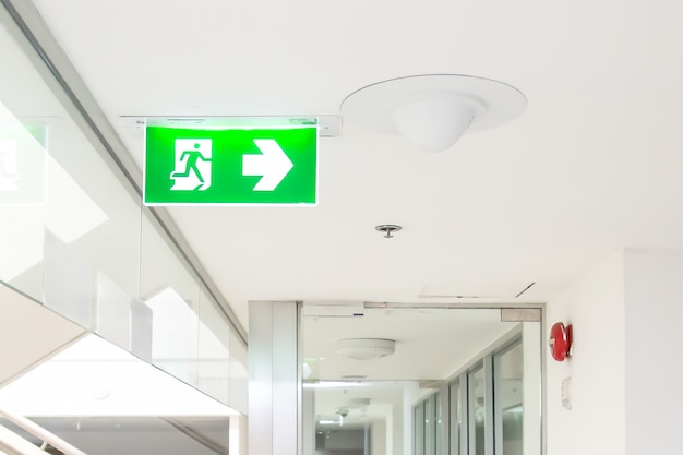 Green emergency fire exit sign or fire escape in the building. Premium Photo