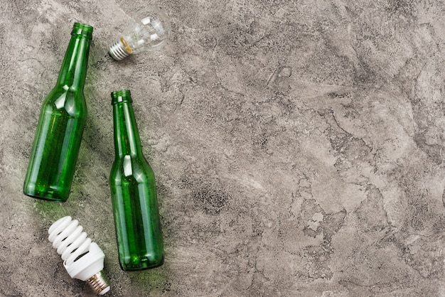 Green empty bottles and used lightbulbs Free Photo