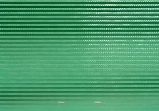Green empty clean roller shutter door warehouse, stripped metal sheet texture of car garage store entrance background Premium Photo