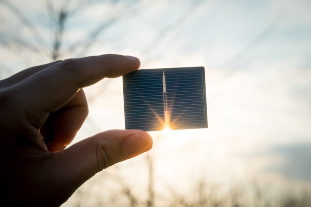 Green energy, photovoltaic solar cell with hand Premium Photo