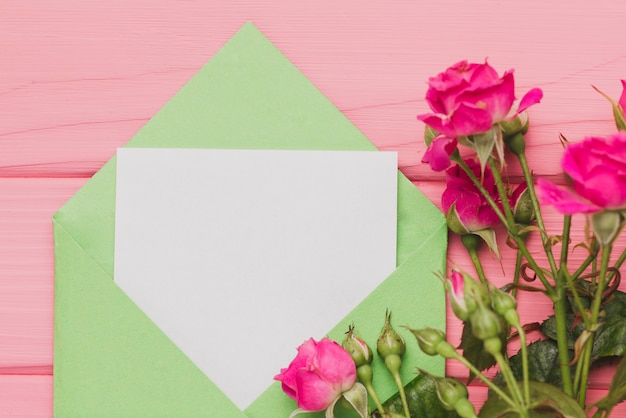 Green envelope with blank note and roses Free Photo