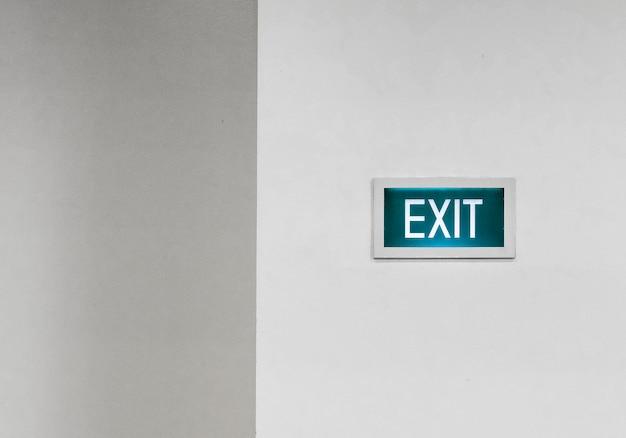 Uscita verde segno su un muro bianco Foto Gratuite
