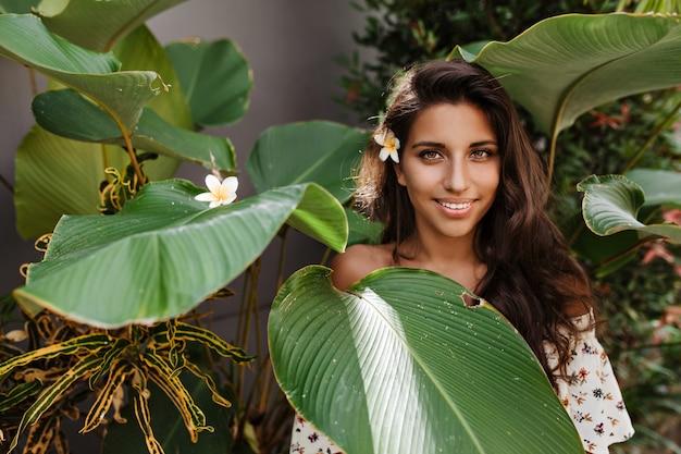 그녀의 머리에 꽃과 녹색 눈동자 갈색 머리 여자는 열대 식물의 큰 잎 사이에서 포즈, 정면으로 보인다 무료 사진