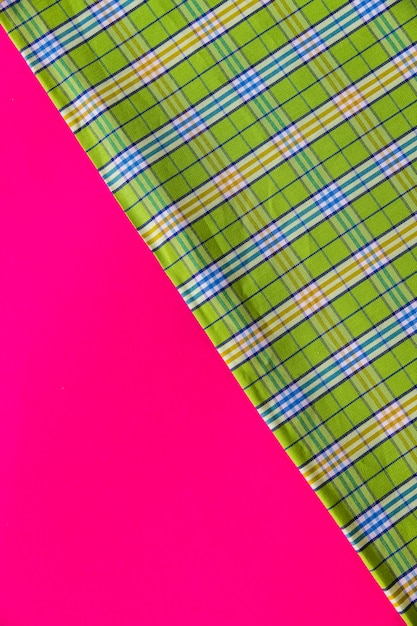 Green fabric material on pink background Free Photo