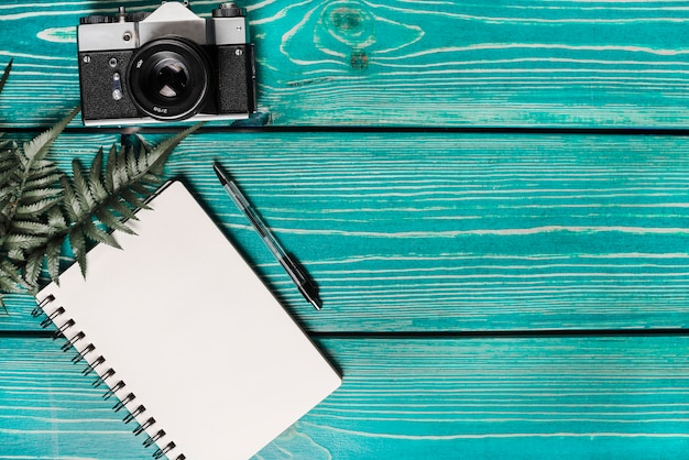 Green fern leaves; spiral notepad; pen and camera against wooden turquoise background Free Photo