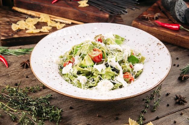 トマトとチーズの木製のテーブルとグリーンフェットチーネパスタ Premium写真