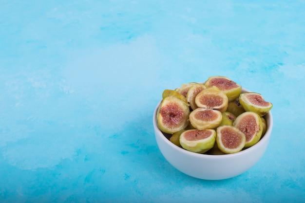 Green figs with red seeds in a white ceramic bowl, angle view. Free Photo