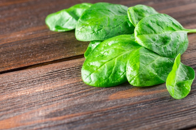 Green fresh spinach leaves on a wooden table. Premium Photo