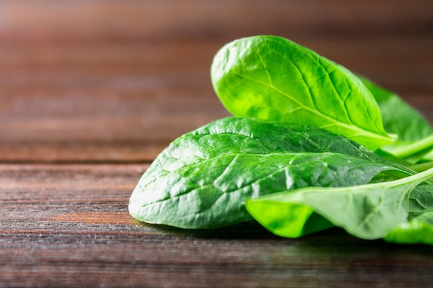 Green fresh spinach leaves on a wooden table Premium Photo