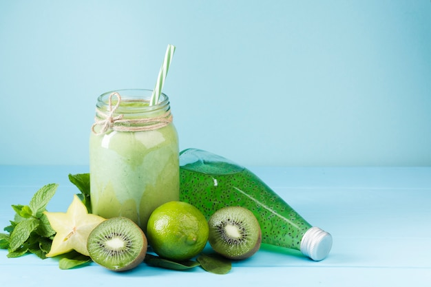 Green fruit smoothie and juice on blue background Free Photo