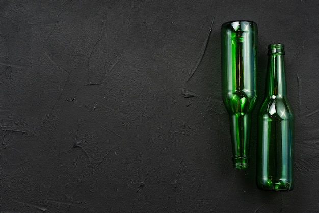 Green glass bottles laying on black background Free Photo