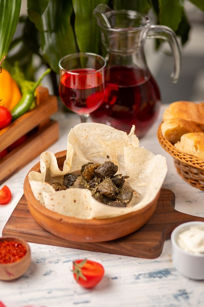 Green grape leaves stuffed with meat, rice, herbs, onion and cooked in olive oil, served with lavash and bread.yarpag dolmasi, yaprak sarmasi. Free Photo