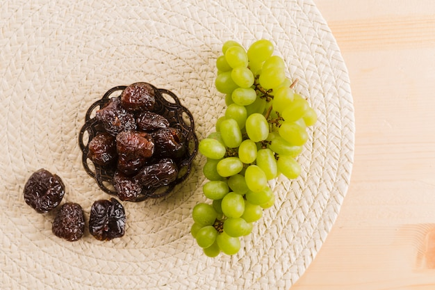 Green grape near prunes on saucer Free Photo