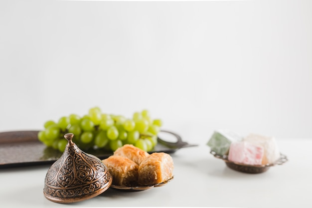 Green grape on tray near baklava and turkish delights on saucers Free Photo
