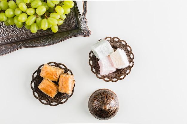 Green grape on tray near baklava and turkish delights Free Photo