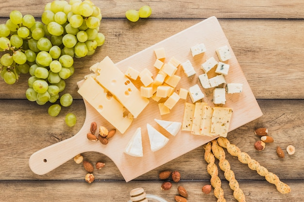Green grapes, almonds, bread sticks and cheese blocks on chopping board over wooden desk Free Photo