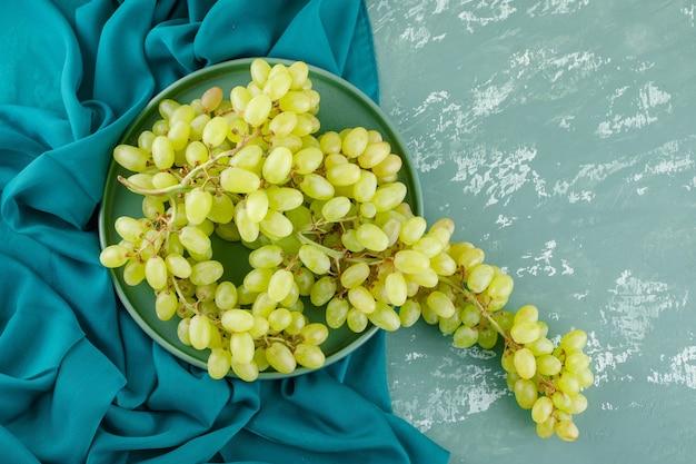 Зеленый виноград в плоском подносе лежит на гипсе и текстиле Бесплатные Фотографии