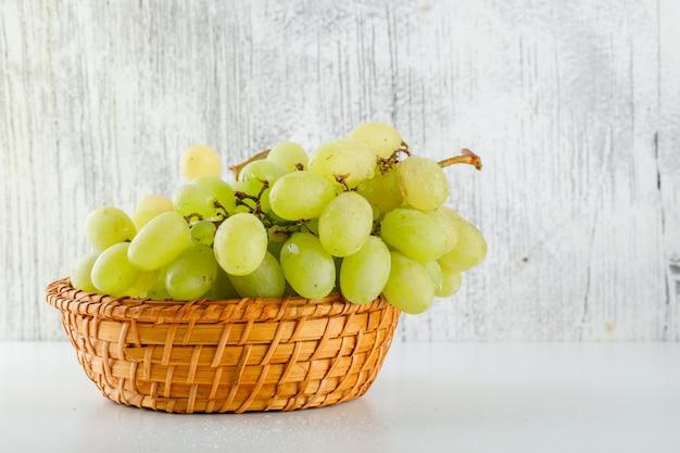 Зеленый виноград в плетеной корзине на белом и шероховатом. Бесплатные Фотографии