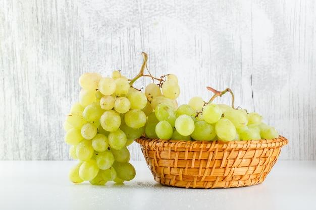 Зеленый виноград в плетеной корзине, вид сбоку на белый и шероховатый Бесплатные Фотографии