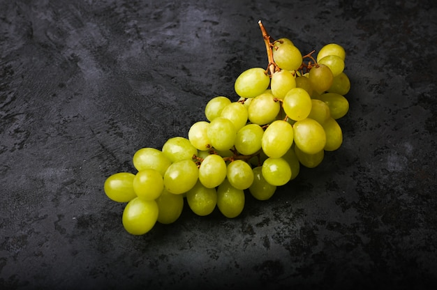Зеленый виноград на темном фоне мрамора. объемный винзавод. гроздь зеленого виноградного куста. Premium Фотографии
