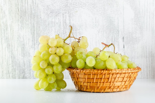 Green grapes in a wicker basket side view on white and grungy Free Photo