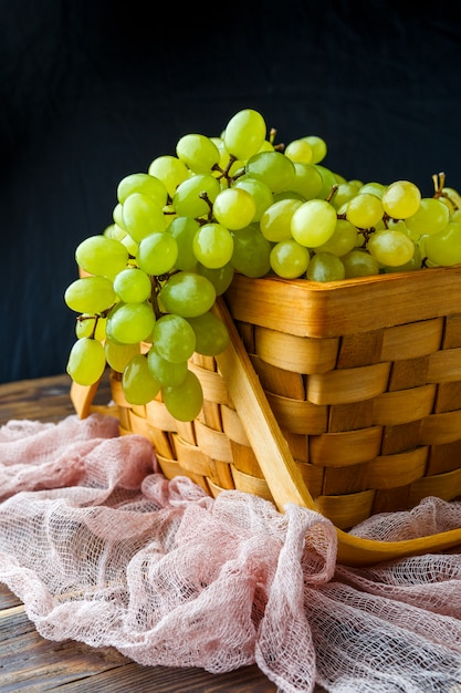 Green grapes in wooden box, on cloth Premium Photo